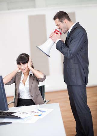 Wütend Geschäftsmann schreiend auf Mitarbeiter im Büro in Megaphon Standard-Bild