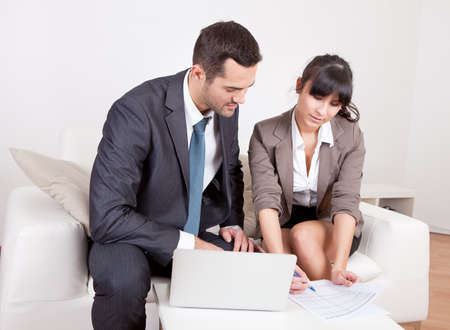 Two business people sitting in the couch discussing Stock Photo - 13019867