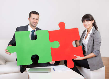 Two business people connecting puzzle pieces at the office. Teamwork concept photo