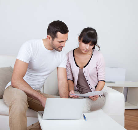 Young couple doing family finances at laptop at home Stock Photo - 13020716