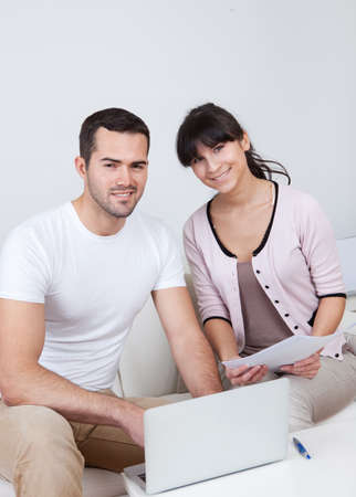 income tax: Young couple doing family finances at laptop at home