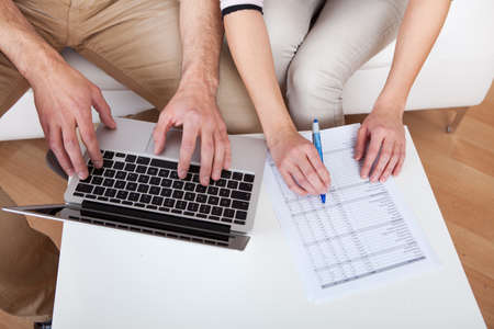 Young couple doing family finances at laptop at home photo