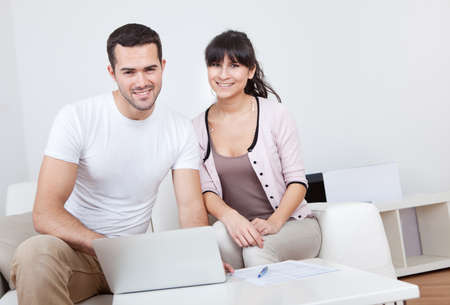 Young couple shopping in internet using laptop at home photo