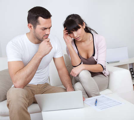 Unhappy young couple in financial trouble at home photo