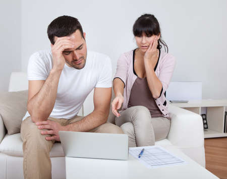 family budget: Unhappy young couple in financial trouble at home