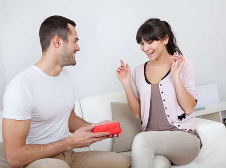 gift giving: Man giving a present to woman at home