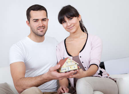 Happy young couple holding a house model and dreaming photo