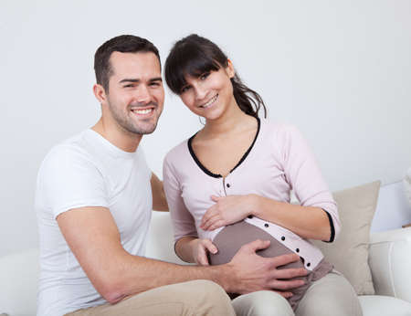Portrait of happy pregnant woman and her husband on sofa at home photo