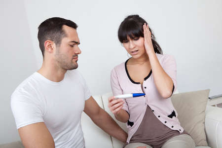 Young couple finding out results of pregnancy test at home photo