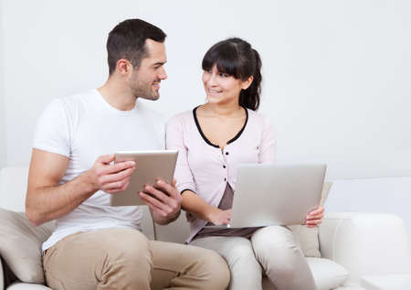 secured payment: Young couple using laptop and tablet in couch at home