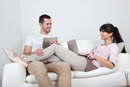 Young couple using laptop and tablet in couch at home photo