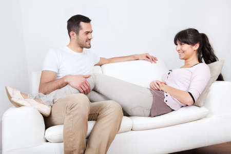 Happy young couple lying it the couch at home Stock Photo - 13020788
