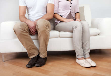 novios enojados: Pareja joven en disputa en casa. Sentado en el sof�