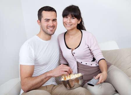pareja comiendo: Pareja joven viendo la televisión en el sofá de casa