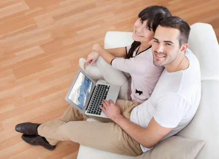 high angles: Young couple watching photos on laptop in couch at home