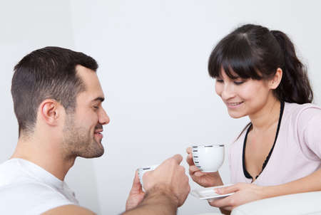 Happy young couple drinking coffee at home photo
