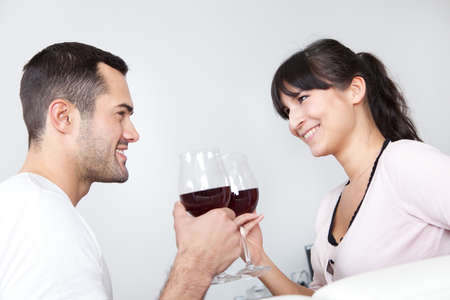 Young couple drinking red wine at home photo