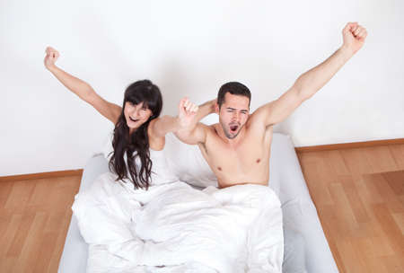 Lovely young couple waking up in bed at home photo