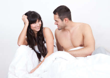 Lovely young couple waking up in bed at home Stock Photo - 13019774