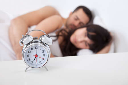 hot love: Close-up on alarm clock and lovely young couple on background