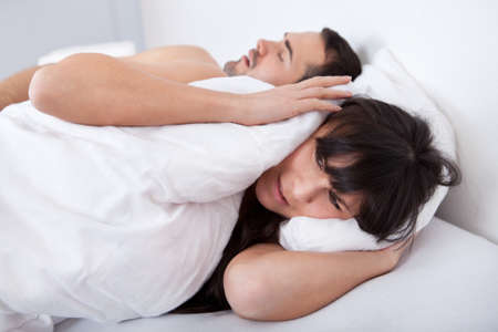 muffle: Young woman suffering from snoring boyfriend in bed