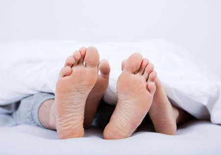 Close-up auf die Füße eines Paares unter der Decke