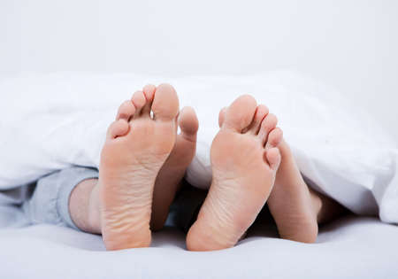 Close-up on feet of a couple under the blanket photo