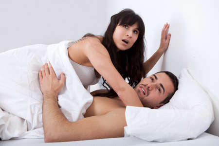 making love: Young couple gets caught while making love in bed Stock Photo