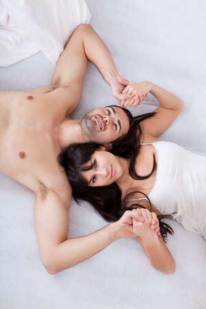 human relationship: Happy young couple lying up in bed