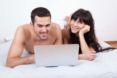 Happy young couple lying up in bed with laptop photo