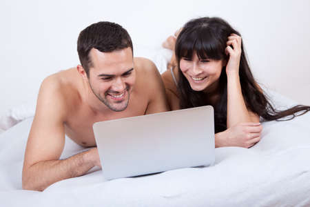 Happy young couple lying up in bed with laptop Stock Photo - 13020500