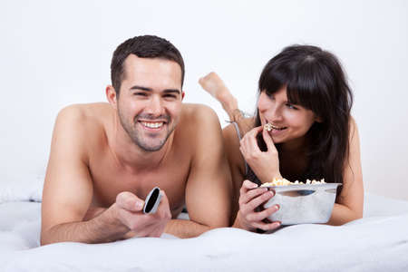 Happy young couple lying up in bed and watching TV photo