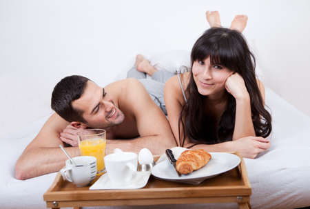 breakfast room: Happy young couple eating breakfast in bed Stock Photo