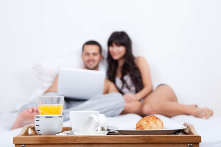 Young couple lying up in bed with laptop and breakfast tray in foreground photo