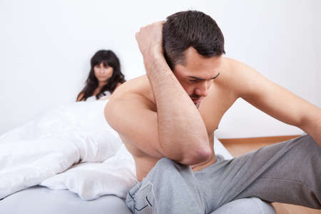 Young couple in quarrel at home. Sitting in the bed photo
