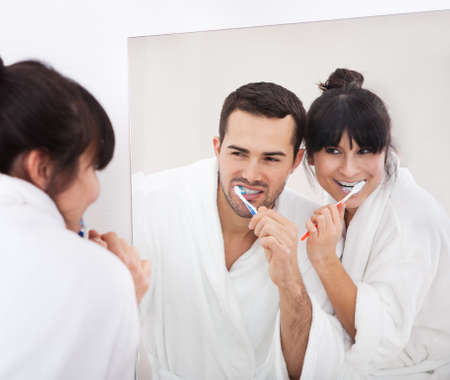 Young couple brushing teeth together at home in the bathroom photo