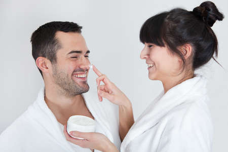 bathroom women: Playful young couple applying cream in the bathroom Stock Photo