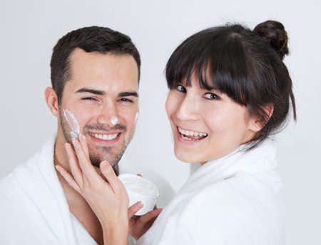 bathrobe: Playful young couple applying cream in the bathroom Stock Photo