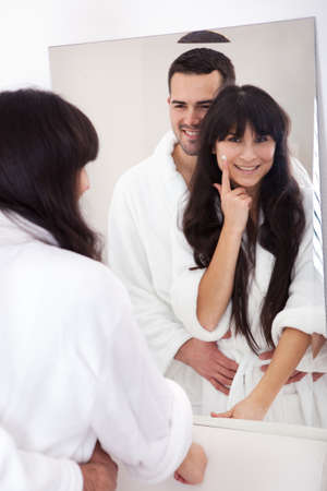 Playful young couple applying cream in the bathroom photo