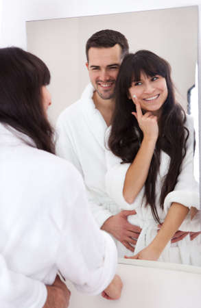 Playful young couple applying cream in the bathroom Stock Photo - 13019786