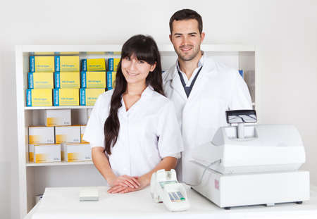 Portrait of two pharmacists at the drugstore smiling photo
