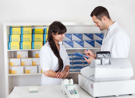 Two pharmacists checking drugs at the drugstore photo