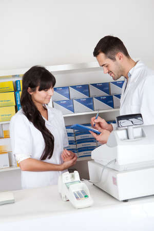Two pharmacists checking drugs at the drugstore Stock Photo - 13020616