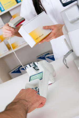 Close-up on hand entering pin code while buying medicine at pharmacy