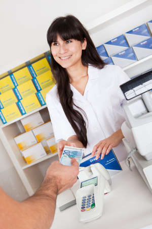 Paying for medicine using cash at pharmacy photo