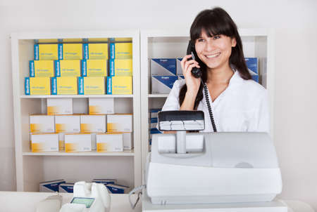 Beautiful pharmacist at the drugstore calling on the phone Stock Photo - 13020720