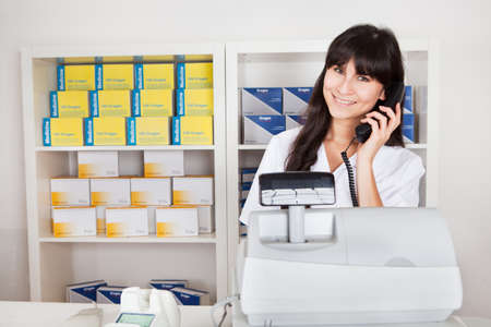 Beautiful pharmacist at the drugstore calling on the phone photo