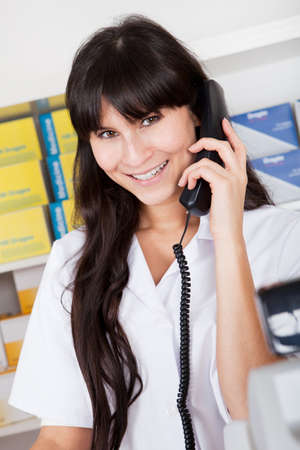 Beautiful pharmacist at the drugstore calling on the phone Stock Photo - 13019868