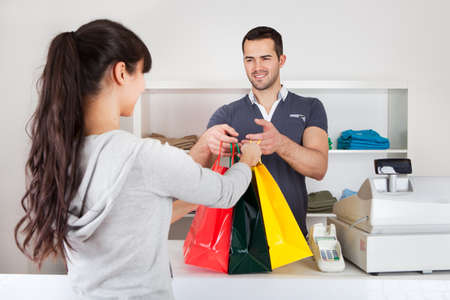 cashier: Female customer buying clothes at retail store
