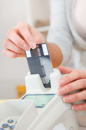 Sales person inserting credit card into scanner photo